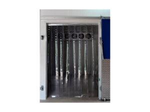 Imagem da cortina de PVC instalada na abertura de uma câmara fria. As tiras flexíveis são transparentes e se estendem do teto até o piso. Ao fundo é possível ver a entrada de ar da câmara fria e na parte direita da foto um pedaço da porta, nas cores azul e cinza.